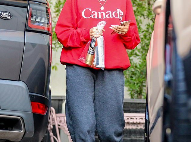 Proud: Hailey Bieber represented the hometown of her husband Justin Bieber by donning a red crew-neck jacket from Canada during a salon trip in Los Angeles on Wednesday.