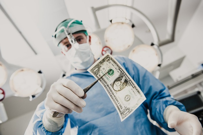 A surgeon holds a $ 1 bill with surgical forceps.