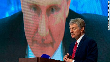 Kremlin spokesman Dmitry Peskov looks at Russian President Vladimir Putin speaking via video link at a press conference.  Both blamed Western intelligence agencies for their involvement with Navalny.