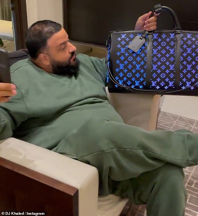 Mobile app: 'So, check this out, that's the app.  I always wanted this bag and my beautiful queen got me this as a gift, '' said DJ Khaled carrying a mobile app while wearing an olive green track suit.