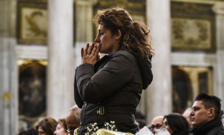 Una donna in preghiera in chiesa