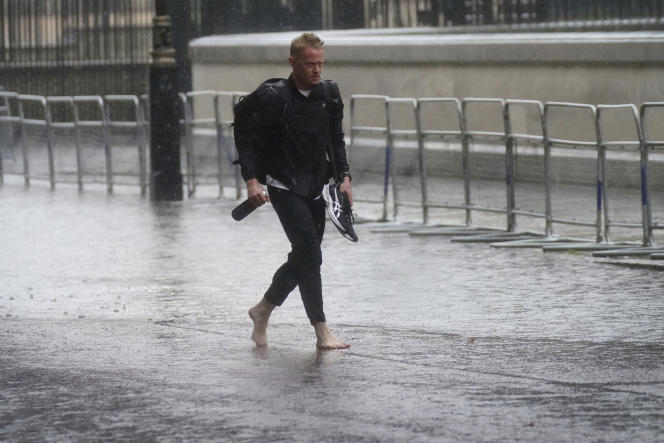 A man walks barefoot on a flooded street in central London on July 25.