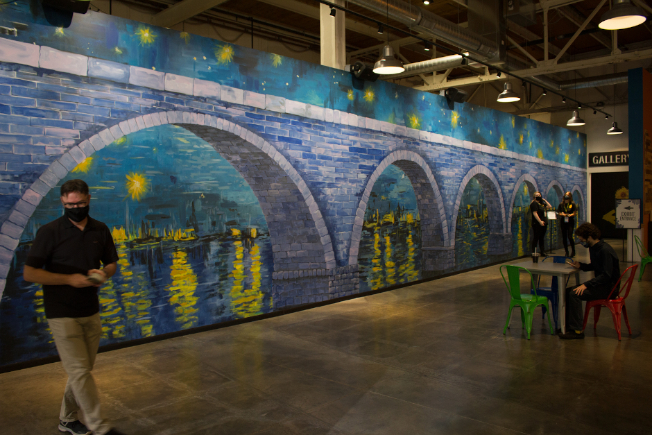 A mural with an arched stone bridge painted in a mysterious style reminiscent of Van Gogh