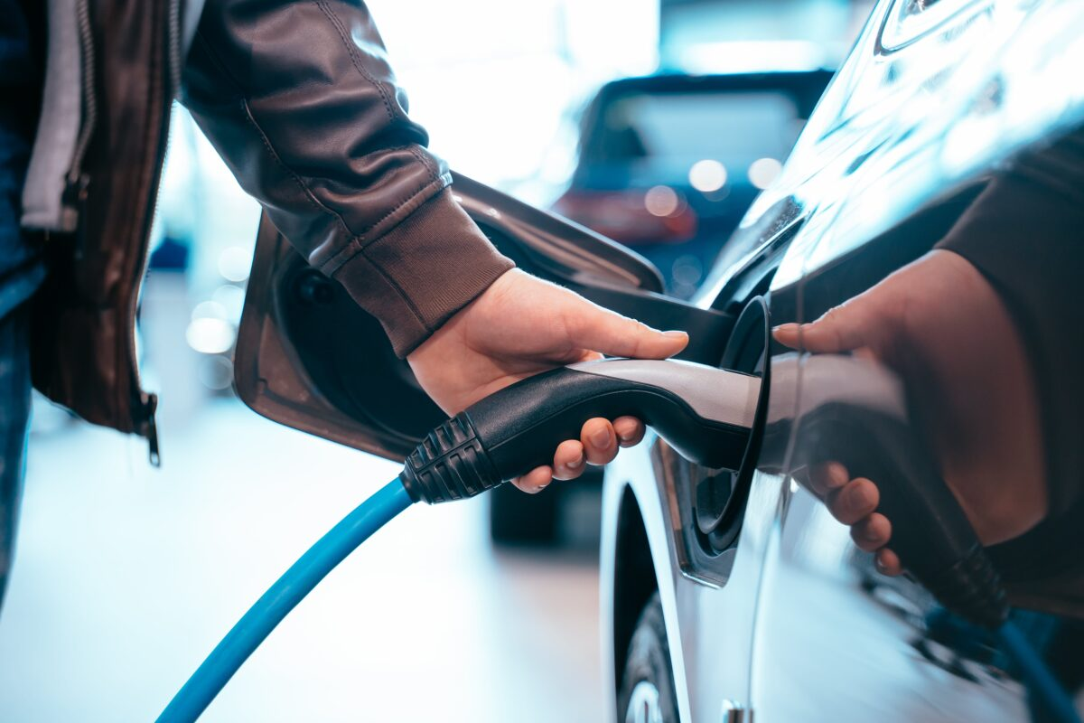 The human hand holds a charging electric car that connects to a micro electric car
