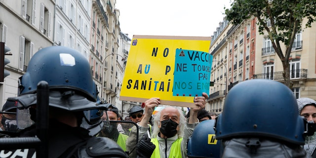 Anti-vaccination protesters confront police during a protest against passports and vaccines, in Paris, France, Saturday, August 7, 2021.